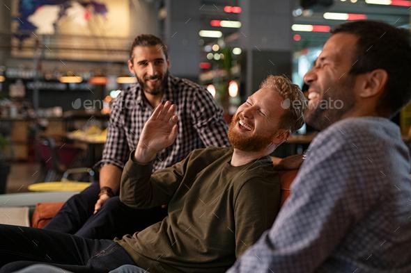 Mid adult men friends enjoying at pub - Stock Photo - Images