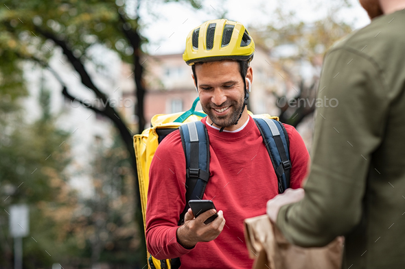 Delivery man checking food order with smartphone - Stock Photo - Images