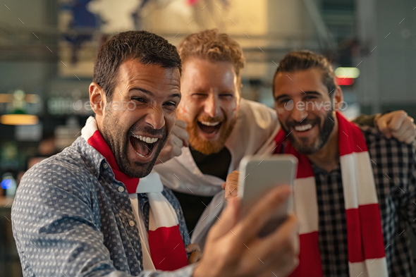Excited supporters watching football match on phone - Stock Photo - Images