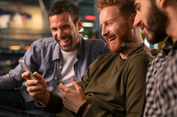 Friends laughing and using smartphone at pub - Stock Photo - Images