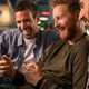 Friends laughing and using smartphone at pub - PhotoDune Item for Sale