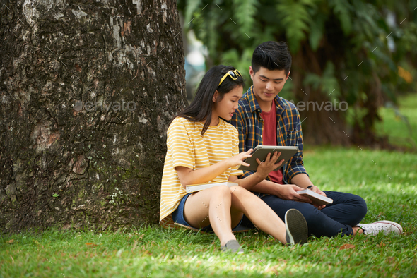 Couple reading something on tablet computer - Stock Photo - Images