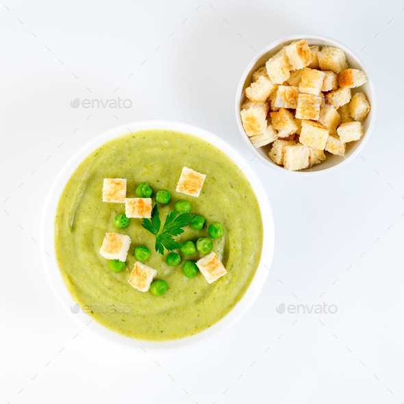 large white bowl with cream soup of broccoli, potatoes and green peas on white background, top view - Stock Photo - Images