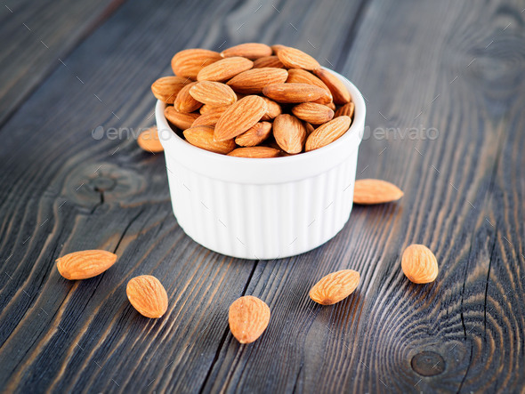 Side view of white bowl with a handful of almond, nuts on a wooden dark background. - Stock Photo - Images
