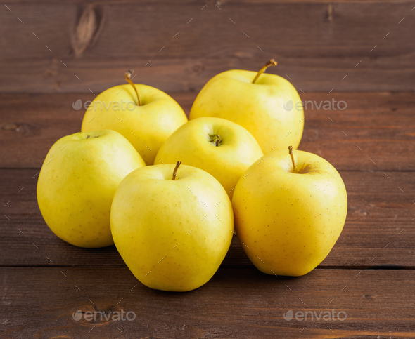 Golden Delicious. Juicy ripe fresh yellow apples on a brown wooden background, side view. - Stock Photo - Images