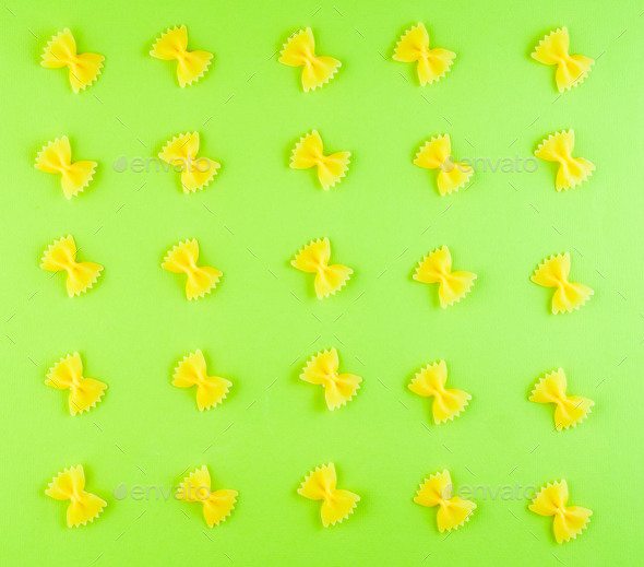 pattern of pasta Farfalle on green background, food ingredient, top view - Stock Photo - Images