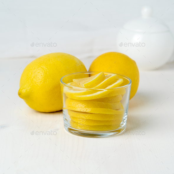 Lemon slice in jar and whole fresh lemons on white wooden background - Stock Photo - Images