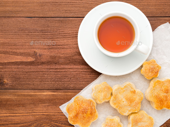 Breakfast with home baking and a Cup of tea on brown wooden table, top view - Stock Photo - Images