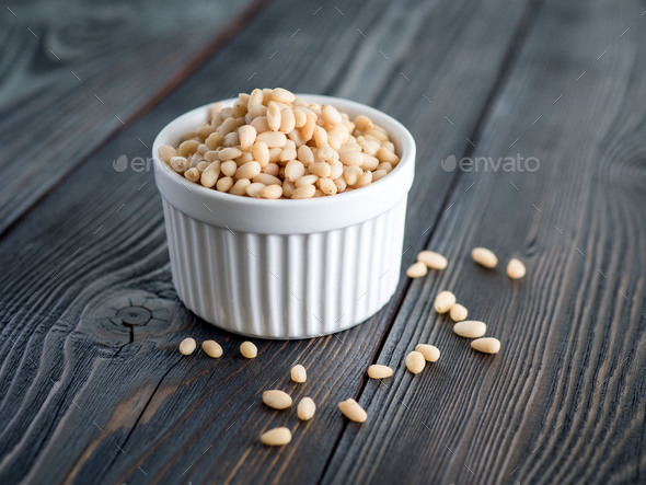 Side view of white cups, bowls with a handful of pine nut, cedar nuts on a wooden background - Stock Photo - Images