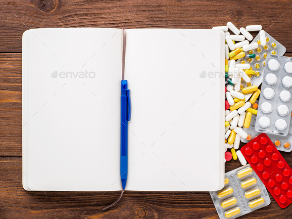 handful of scattered medicines, pills and tablets and note pad on brown wooden background - Stock Photo - Images