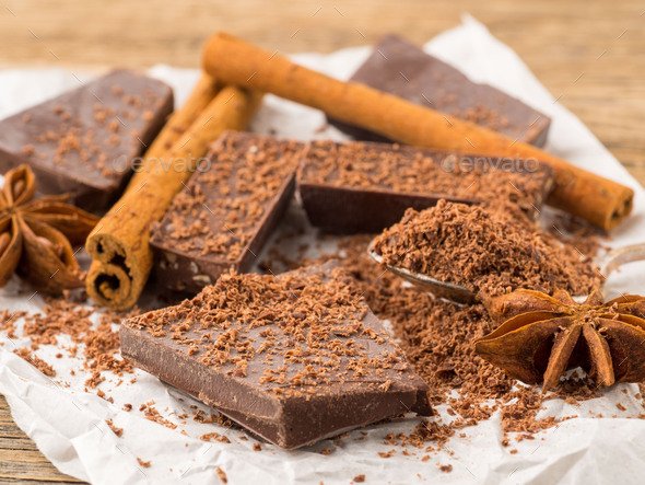 broken pieces of chocolate, anise star, cinnamon sticks, crumb on parchment paper - Stock Photo - Images