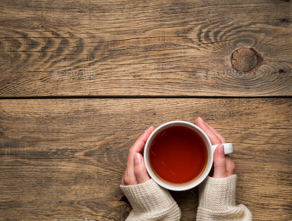 Female hands holding a mug of hot black tea. Cold winter - Stock Photo - Images
