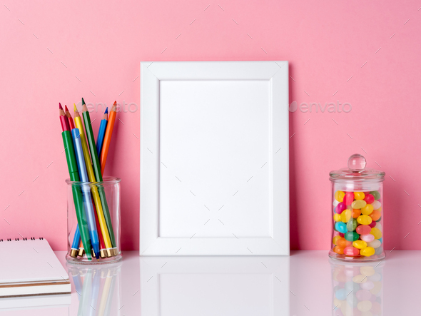 Blank white frame and crayon in jar, candys on a white table against the pink wall with copy space - Stock Photo - Images