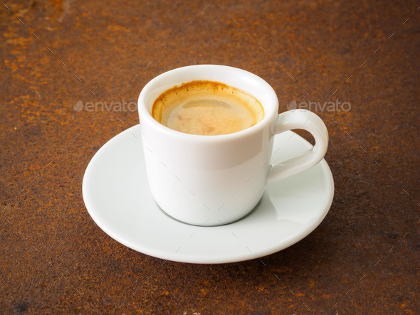 black frothy coffee with foam in white cup with plate on  rusty metal table, side view - Stock Photo - Images