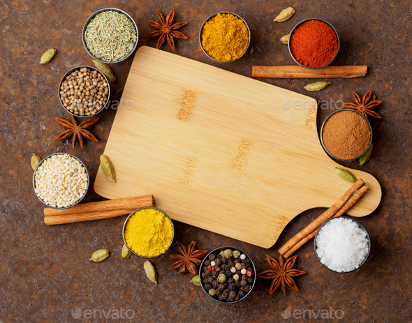 Various Indian spices in metal cups. Empty wooden Board, top view, space for text. - Stock Photo - Images
