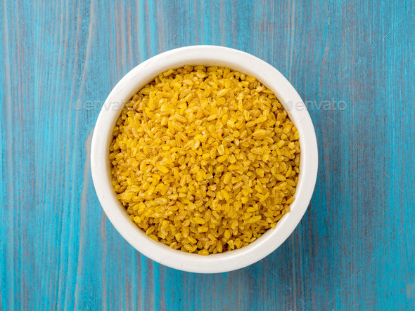 White bowl with raw bulgur on blue wooden background. Top view. - Stock Photo - Images