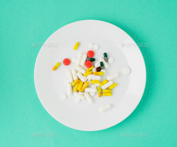 handful of scattered medicines, pills and tablets on white plate on blue background - Stock Photo - Images