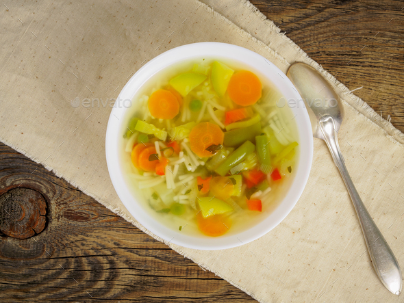 Bright spring vegetable dietary vegetarian soup, linen napkin, top view, wooden background. - Stock Photo - Images
