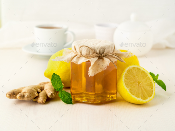 Popular ways to treat a cold - a jar of honey, ginger, mint, lemons on white background, side view - Stock Photo - Images