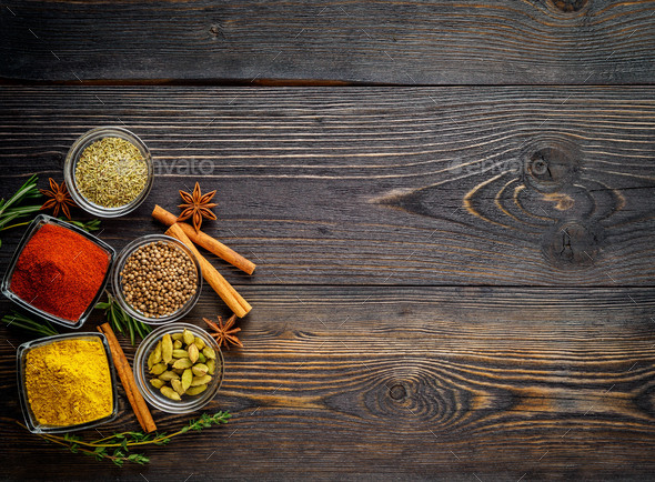Set of spices and herbs on dark brown textured wooden table. Top view, empty space - Stock Photo - Images