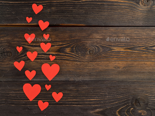 Lots of red paper hearts on a dark brown rustic weathered wooden background, top view - Stock Photo - Images