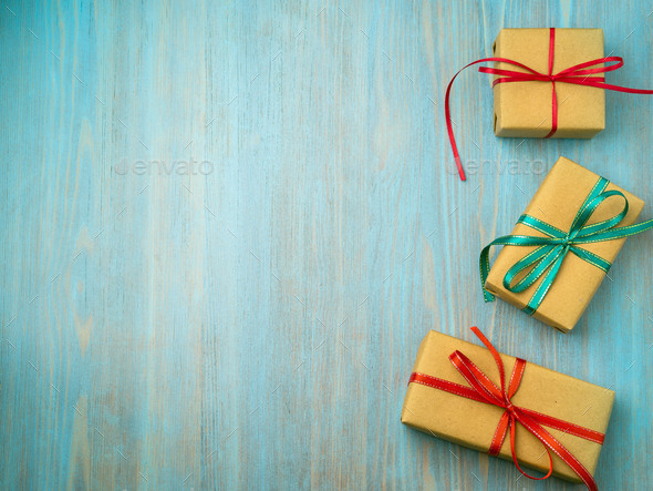 gift packaging box with ribbons of red and green on a wooden blue-green table - Stock Photo - Images