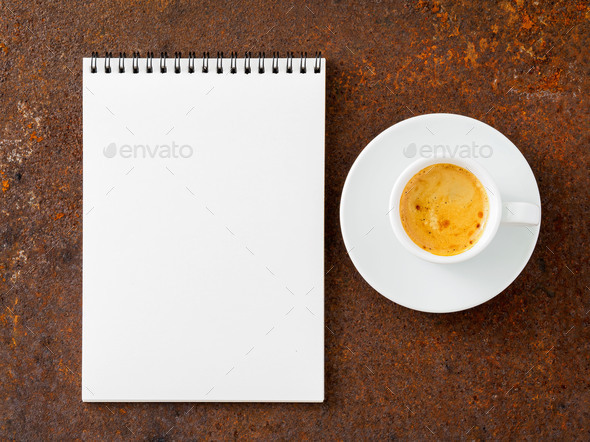 blank sheet of notebook with a spiral and cup of coffee on rusted old iron table, top view. - Stock Photo - Images