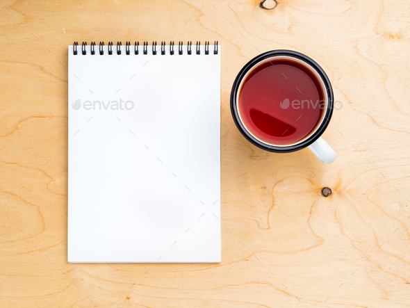 metal mug with tea, empty a blank sheet of notepad on the spiral on a beige wooden background - Stock Photo - Images