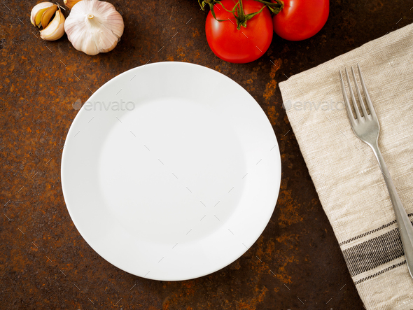 clean empty white plate and fork on linen napkin on rusted old iron table - Stock Photo - Images