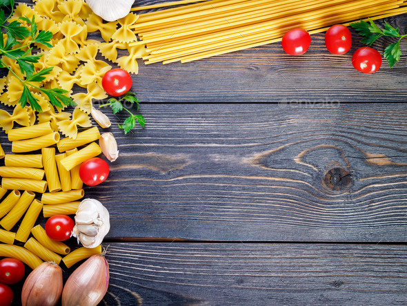 pasta, tomatoes, shallots, garlic, parsley on dark wooden background, top view, copy space. - Stock Photo - Images