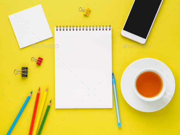 Top view of modern bright yellow office desktop with blank notepad, cup of tea and supplies - Stock Photo - Images