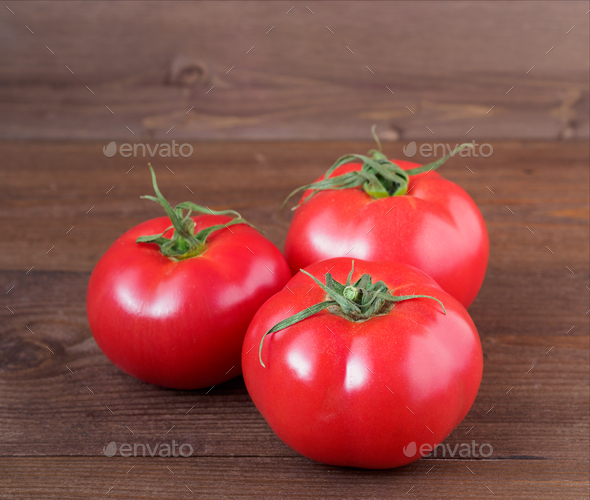 three ripe fresh red tomatoes on wooden brown background - Stock Photo - Images