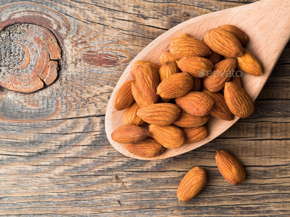 large wooden spoon with a handful of nuts of almonds on a wooden table, top view, closeup - Stock Photo - Images