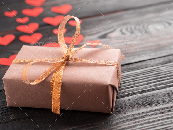 gift box with ribbon and lots of little red hearts on wooden texture dark background, side view - Stock Photo - Images