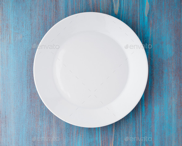 big flat empty white plate on a blue wooden table, top view - Stock Photo - Images