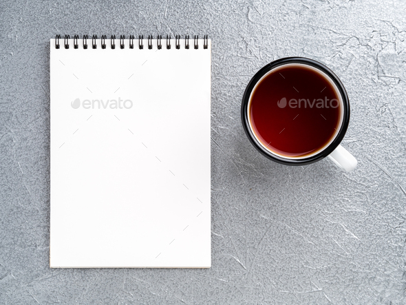 metal mug with tea, empty a blank sheet of Notepad on the spiral on a gray metallic background - Stock Photo - Images