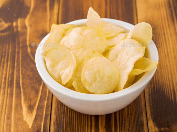potato chips in white bowl on brown wooden table - Stock Photo - Images