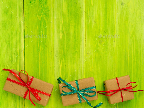 gift box wrapped with Kraft paper in bright green wooden background - Stock Photo - Images