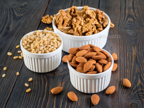 assorted nuts in white bowl on wooden dark background, mix of walnuts, almonds and cedar, side view - Stock Photo - Images