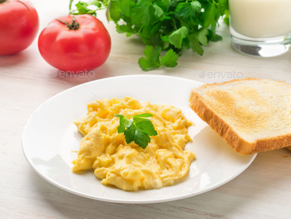 white plate with pan-fried scrambled eggs - Stock Photo - Images