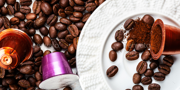 Espresso coffee capsules or pods and coffee beans on grey background - Stock Photo - Images