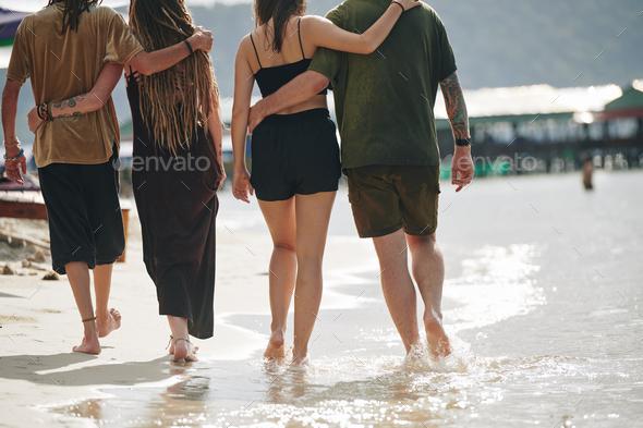 Couples walking along sandy seashore - Stock Photo - Images