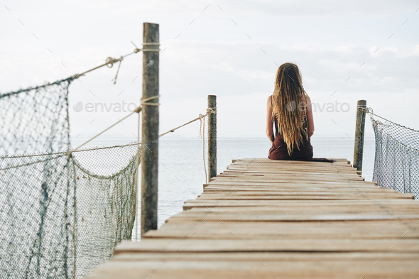 Pensive woman on wooden pier - Stock Photo - Images