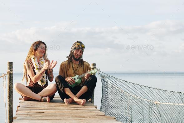 Woman clapping to husband playing ukulele - Stock Photo - Images