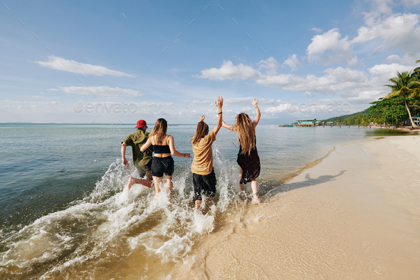 Young people running and splashing on the beach - Stock Photo - Images