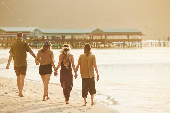 Couples enjoying walking on beach - Stock Photo - Images