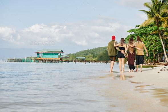 Hugging people walking along seashor - Stock Photo - Images