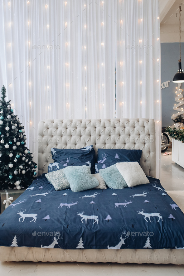 Tidy bed with Christmas tree and garland - Stock Photo - Images