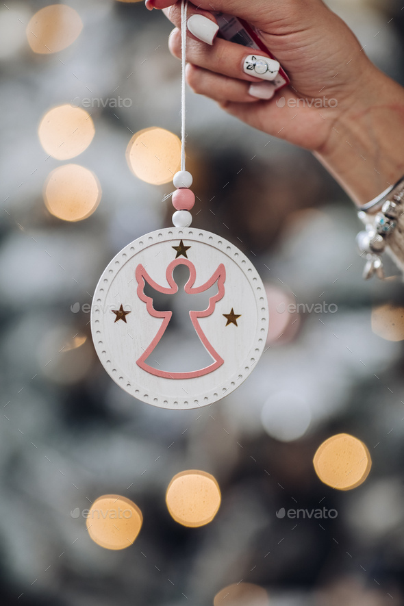 Close up of woman hand with angle toy for the Christmas tree - Stock Photo - Images