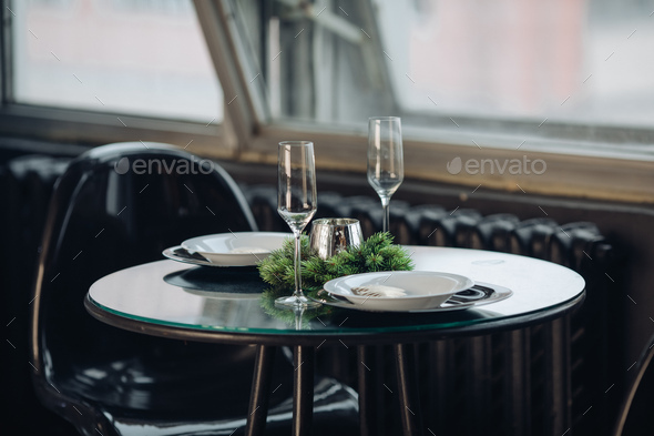 Romantic dinner for two at Christmas. plates against classic sofa in modern apartment - Stock Photo - Images
